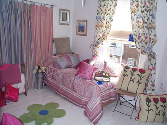pink patchwork quilt with striped curtains and floral curtains