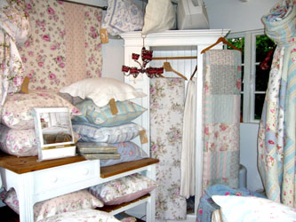 victorian painted wardrobe with display of lace  duvet covers and tablecloths